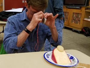 Peter measures the strike and dip on a wedge of cheese